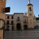 La Torre del Reloj de Yecla, separa el antiguo Pósito y la Antigua Lonja, quedando en medio la cuadrada Torre.